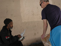 Steve Walczak, right, an assistant professor in information systems, hands a basic needs kit to a homeless man in Denver
