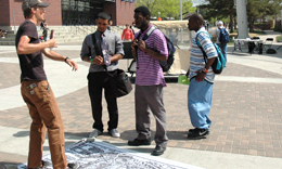 Students for social justice stand near a banner featuring social justice themes near Tivoli Student Union