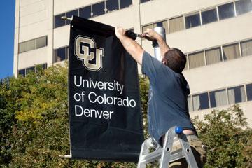 Crews install new CU Denver banners.