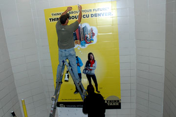 Installation crew puts up CU Denver Think Tank poster in a stairwell at Hinkley High School