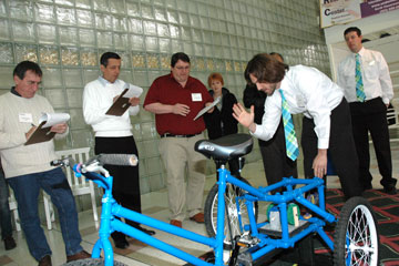 Engineering student Ryan Reece explains features of the TheraGO tricycle to judges at the Senior Design Competition