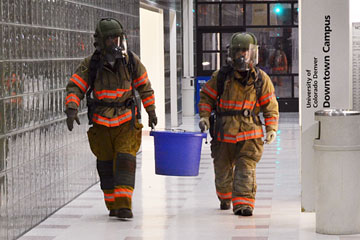 Hazardous materials crew members remove a chemical from the North Classroom