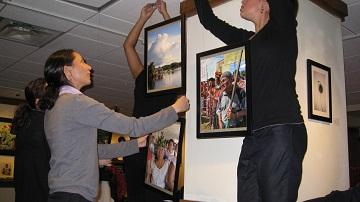 Students hang photos for Un/Shared event