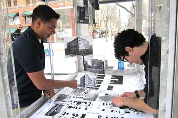 CAP students Ryan Sagar and Jake Sacks install a display into a kiosk on the 16th Street Mall