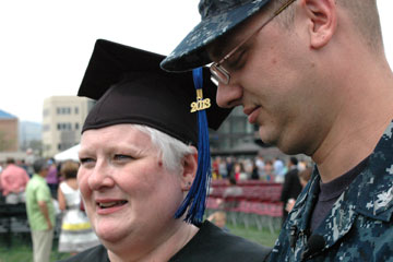 Spring graduate Beth Rozinek stands next to her son Zac Drake at CU Denver graduation May 18