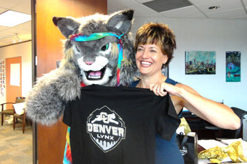 Denver Metro Chamber President Kelly Brough poses with Milo and a lynx shirt in her office