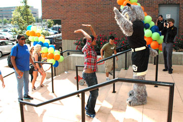 CU Denver student Jade Chatman high-tens Milo the Lynx at move-in day at Campus Village