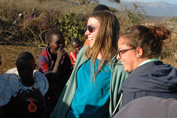 Students Tracey Lancaster and Elanor Sonderman laught as girls from a Masai tribe get them to participate in a dancing ritual.