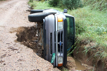 A truck lies on its side after a road in Sunshine Canyon gives way due to flooding