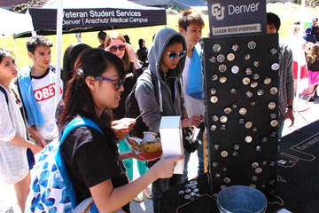 CU Denver students crowd around the Learn with Purpose button display at a Spring Fling booth
