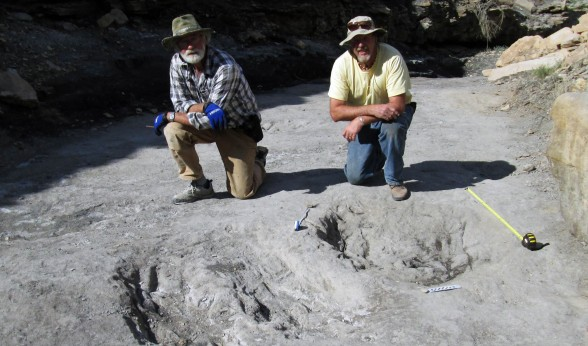 Martin Lockley (right) and Ken Cart pose beside large dinosaur scrapes in western Colorado