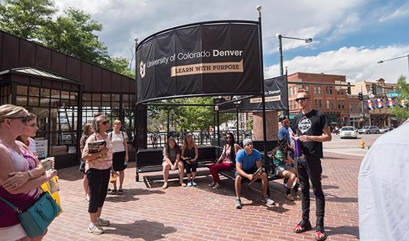 Student Ambassador Matt Stark talks to tour members before walking across to Larimer St.