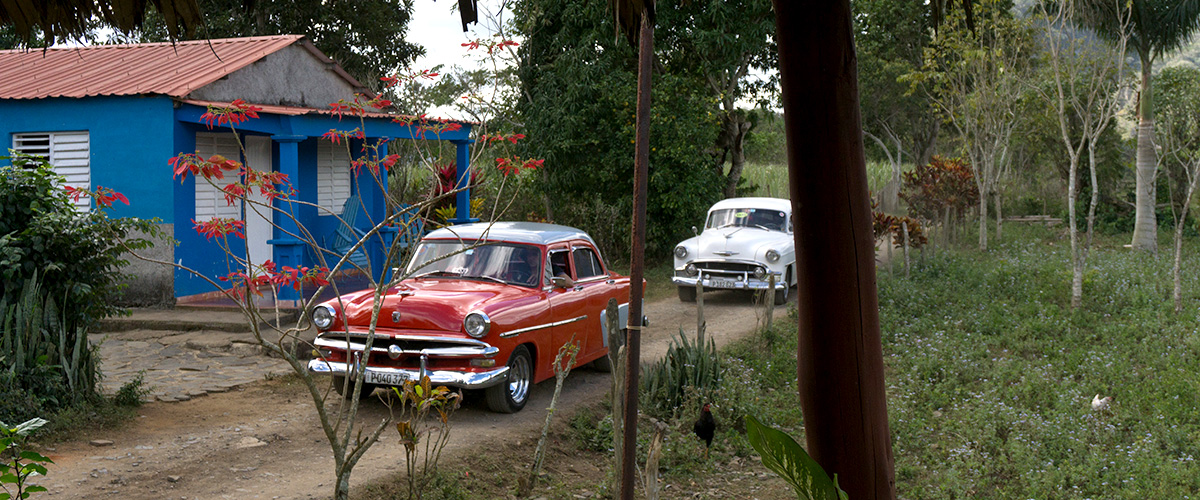 Classic cars on dirt road in Cuba
