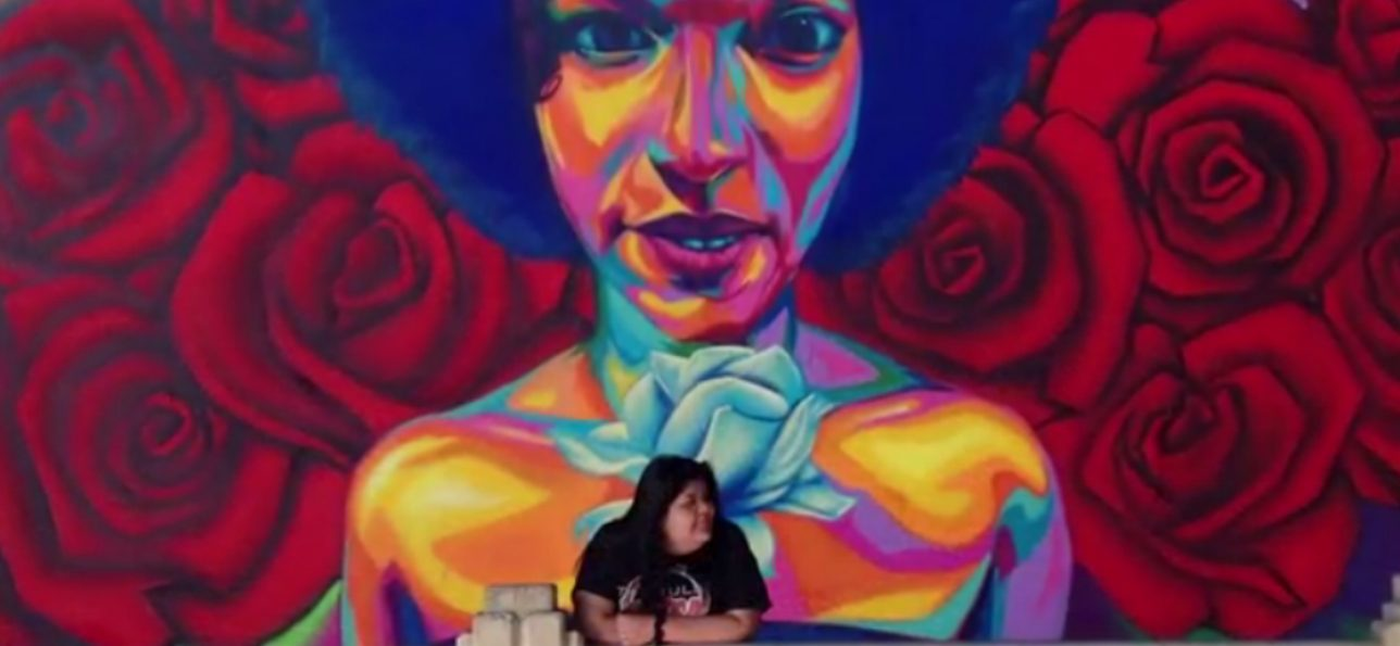 Esme Aguilar, a youth participant, poses in front of a mural