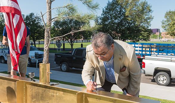 Raul Cardenas, CU Denver vice chancellor for Student Affairs, signs beam