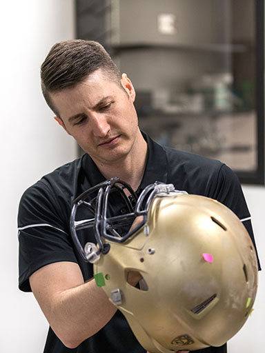 Professor Chris Yakacki and football helmet