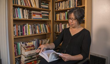 Professor of English Cynthia Wong reads in her office.