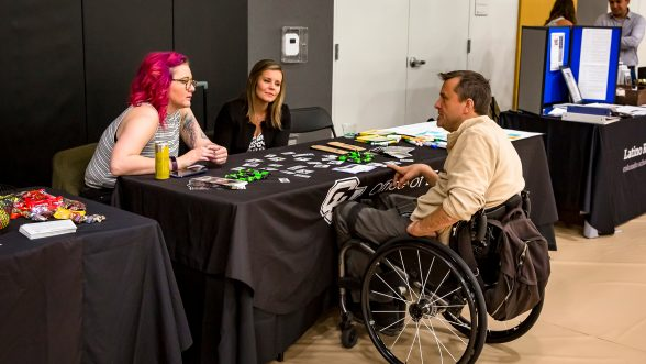 Two women talk over table with man in wheelchair