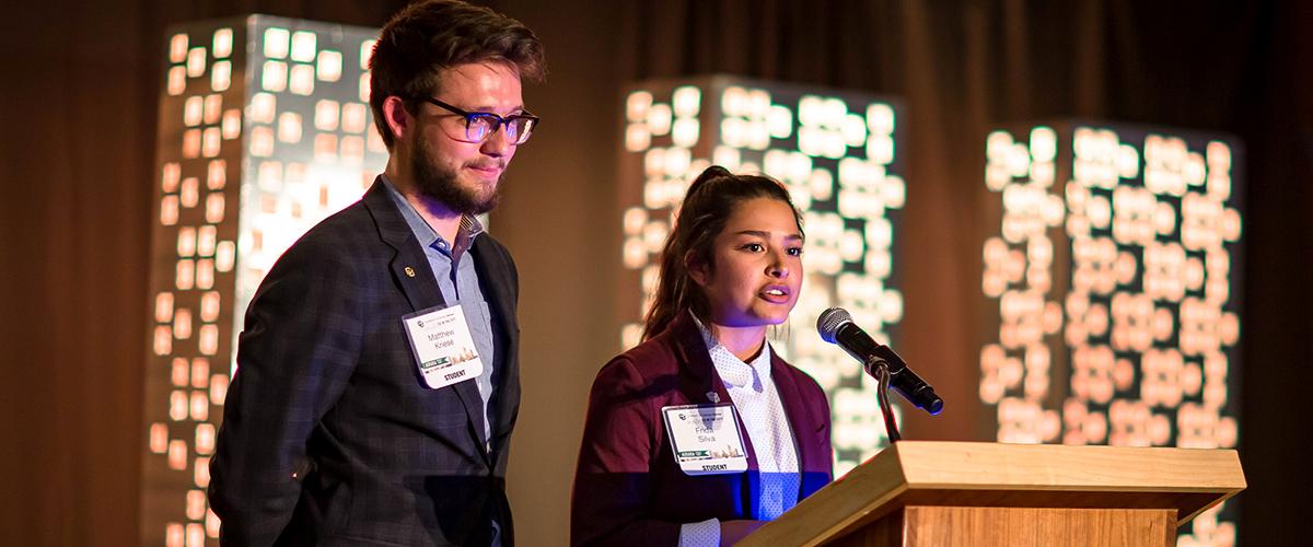 Matthew Kriese and Frida Silva stand at podium