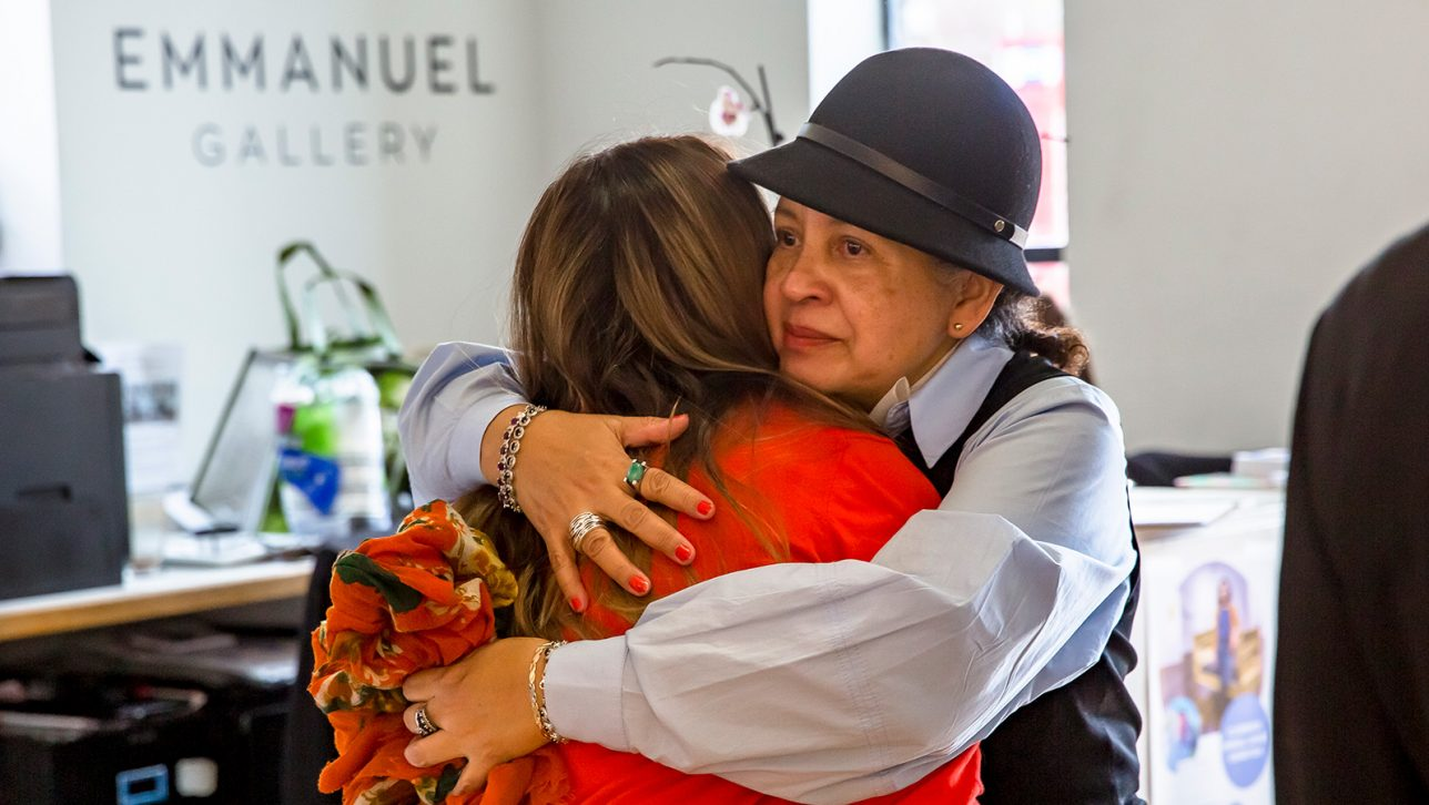 Two women hug at community gathering