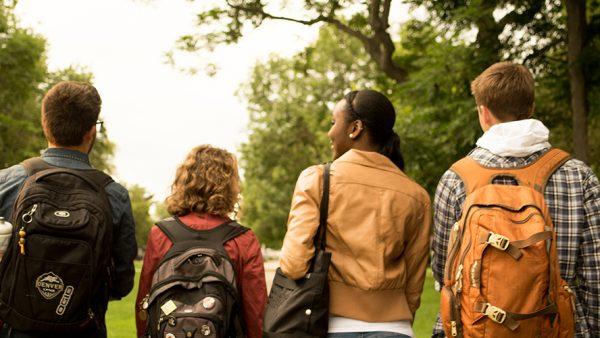 Four students walking together near trees