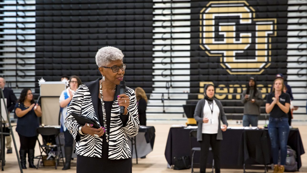 Brenda Allen speaks at conference in front of bleachers with big CU logo