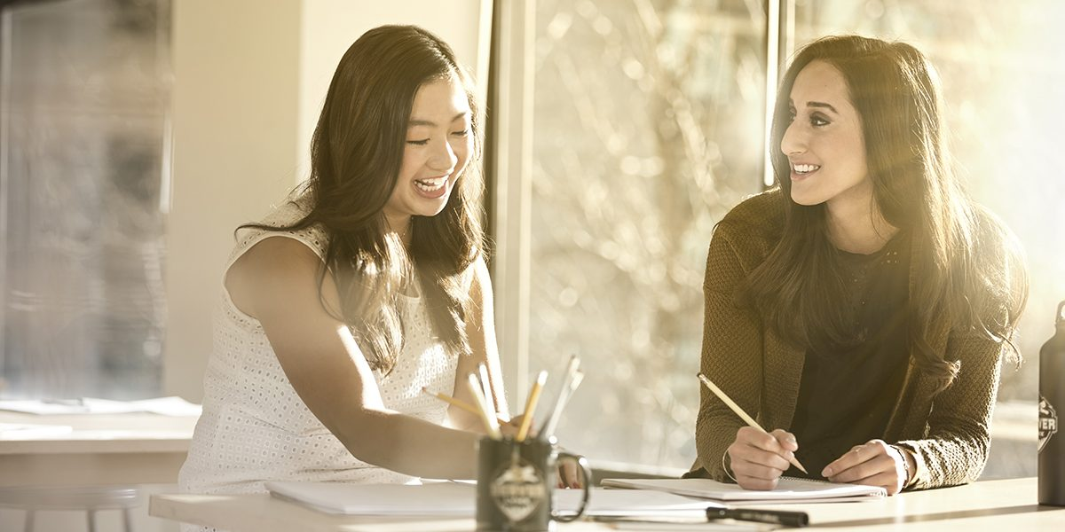 Two women writing at desk