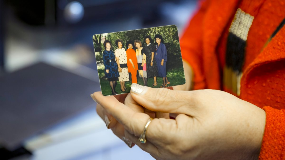 Gloria holding a photo of her and her five sisters.