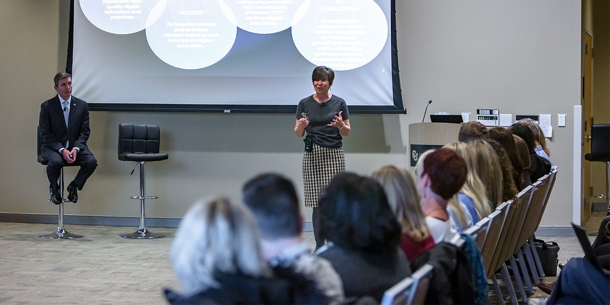 Woman standing in front of a PowerPoint talking to the audience.