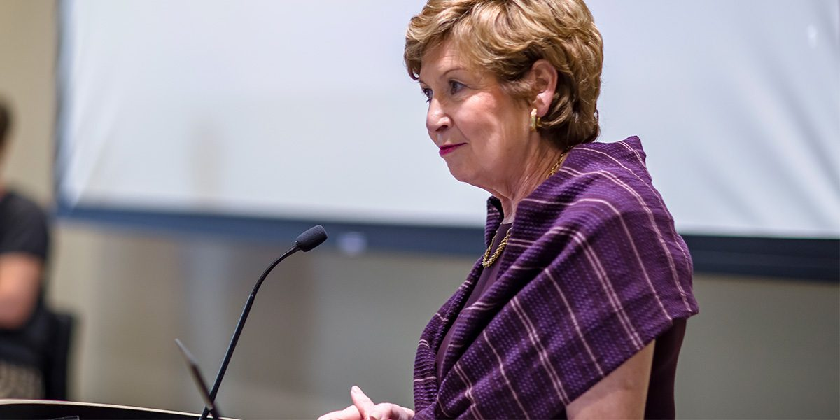 Chancellor Dorothy Horrell speaking in front of a microphone.