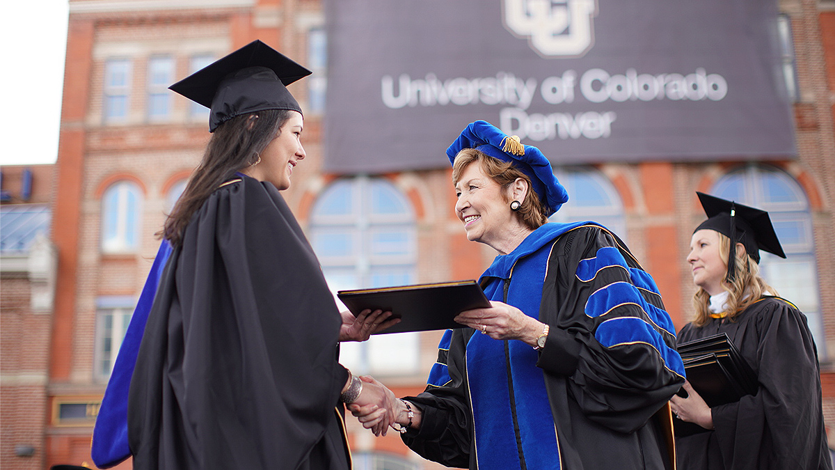 Chancellor Horell hands a female graduate her diploma.