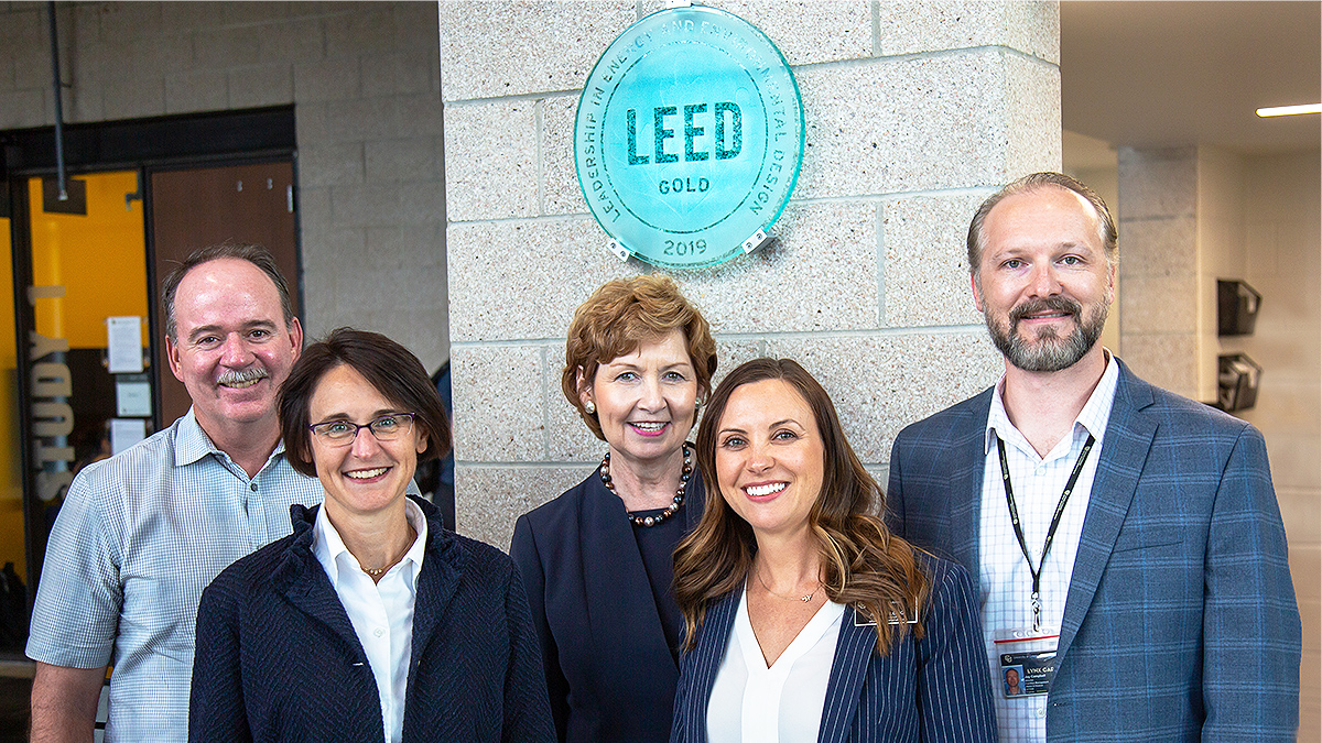 Five people under LEED plaque