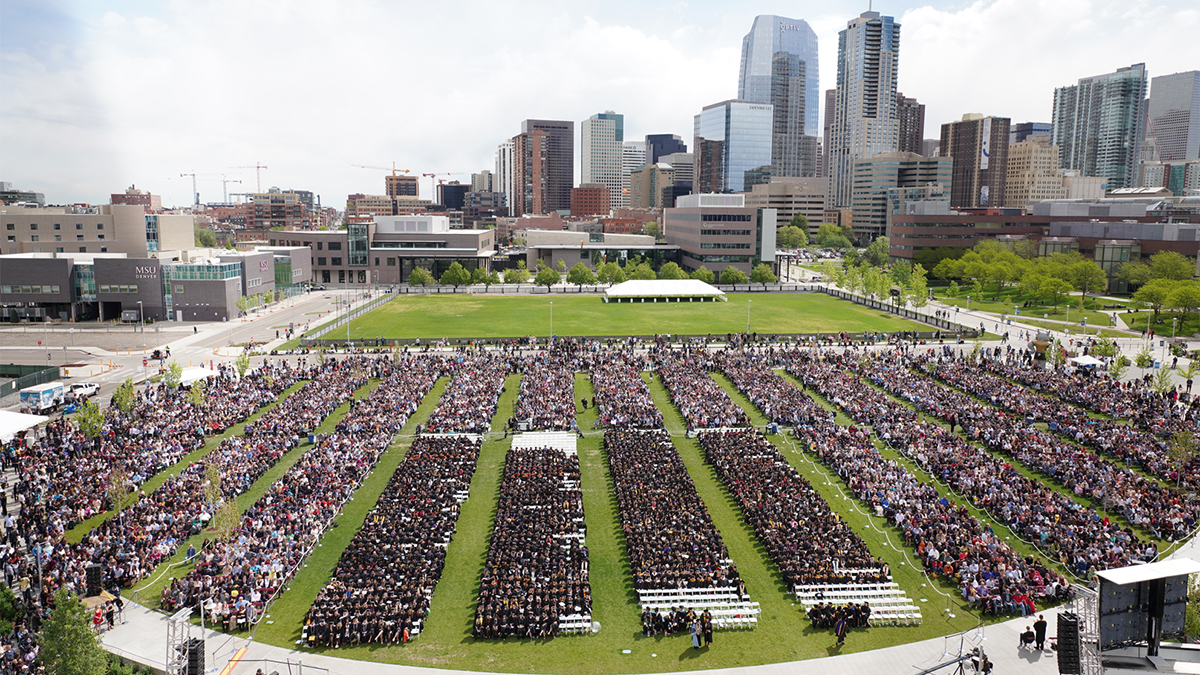 Aerial view of commencement on campus and a city view in the background.