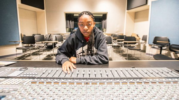 """Bradlie """"Jelie"""" Jones sits in a classroom with her hand on a digital audio workstation."""