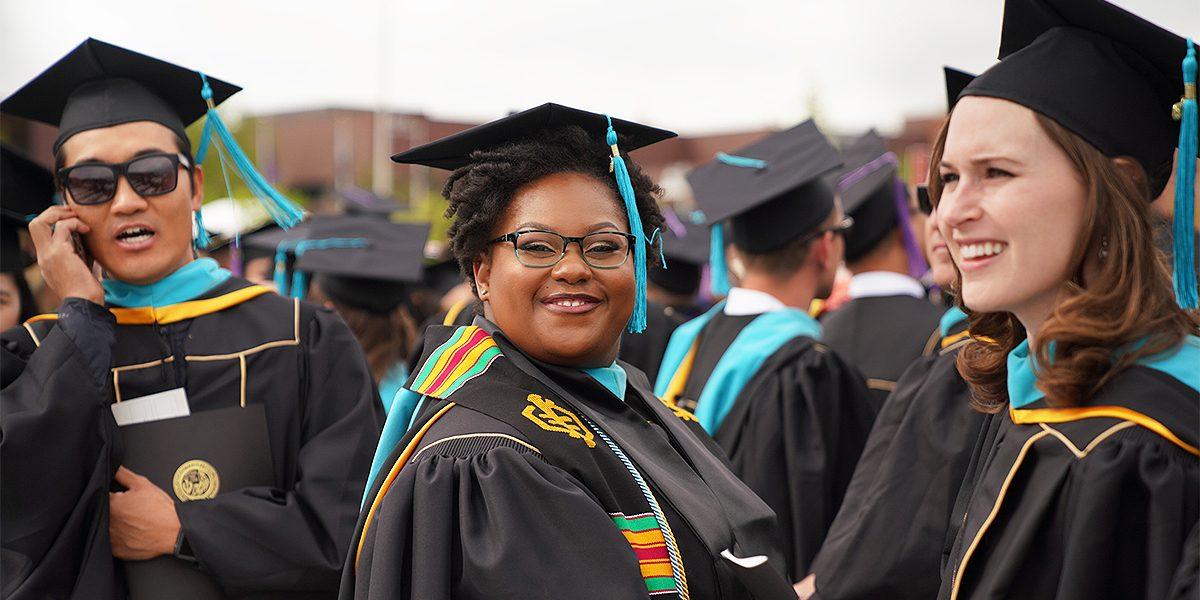 A female graduate smiles at the camera.