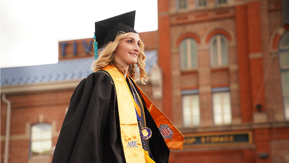 Female graduate walks up to receive her diploma in front of Tivoli.