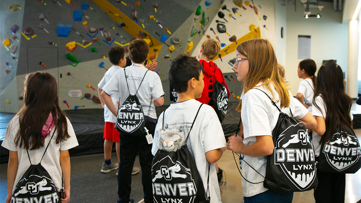 Group of children stand in front of the rock climbing wall each wearing matching CU Denver Lynx drawstring bags.