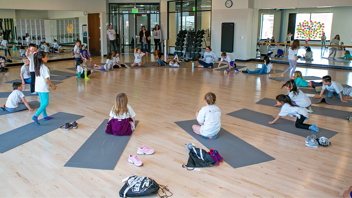Children are seated on the floor with yoga mats while looking at the instructor