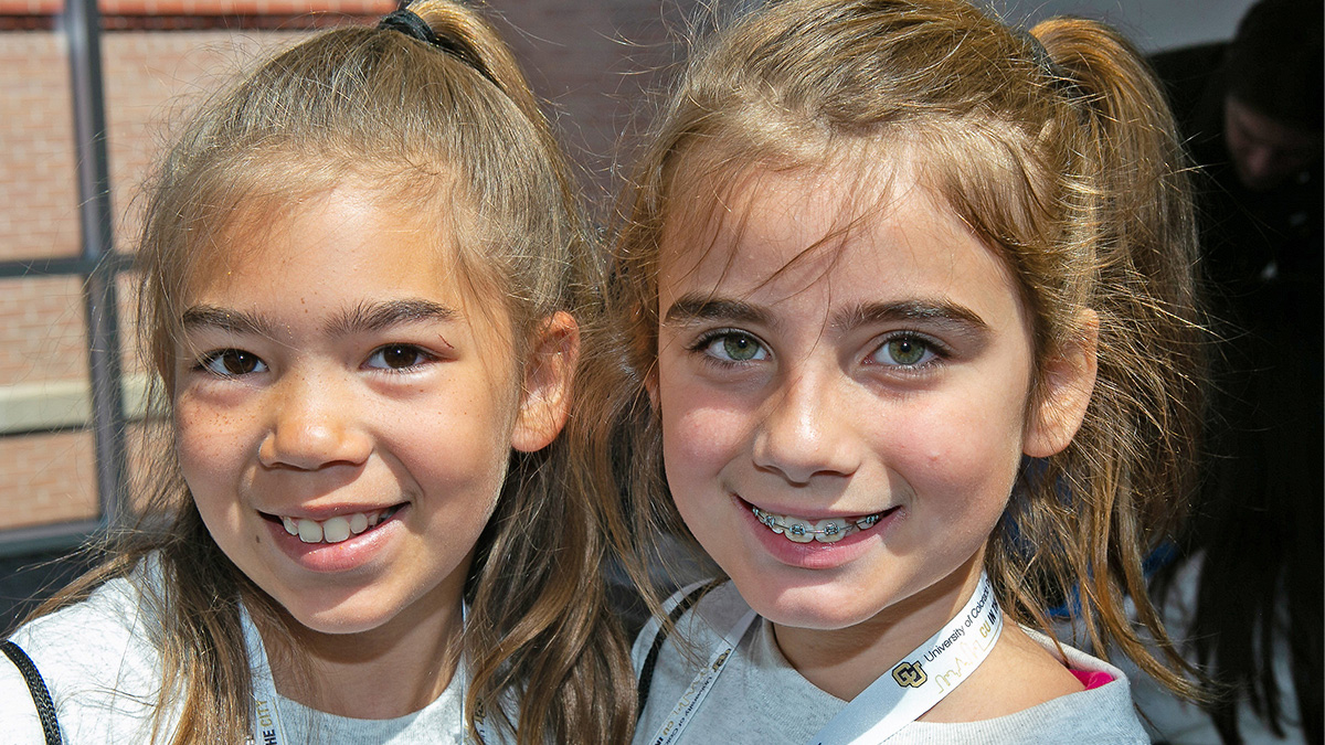 Two girls with CU Denver lanyards smile for the camera.