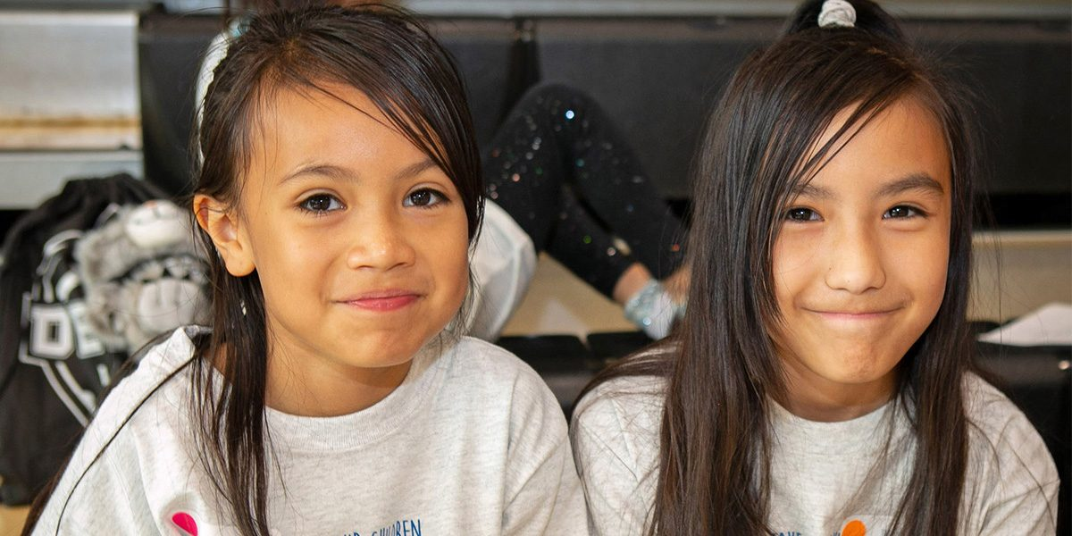 Two girls smile at the camera while sitting on the bleachers of the gymnasium.