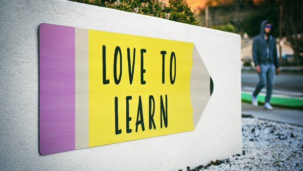 """""""Love to learn"""" quote on yellow cardboard pencil."""