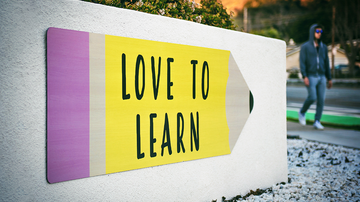 """Love to learn"" quote on yellow cardboard pencil."