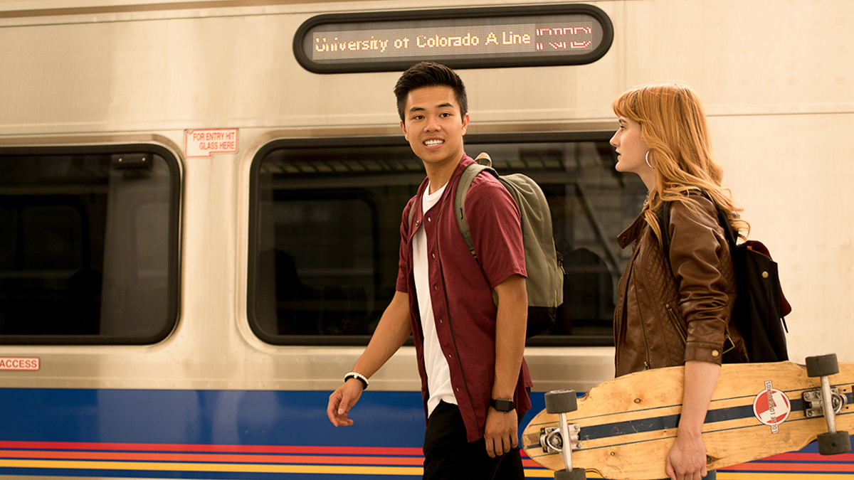 Two students talk and walk next to the light rail.