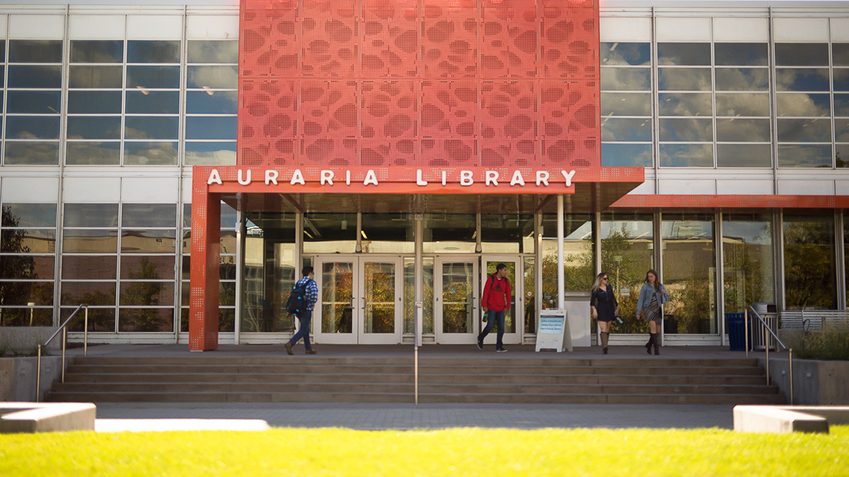 Auraria Library exterior view with students walking in and out of the entrance.