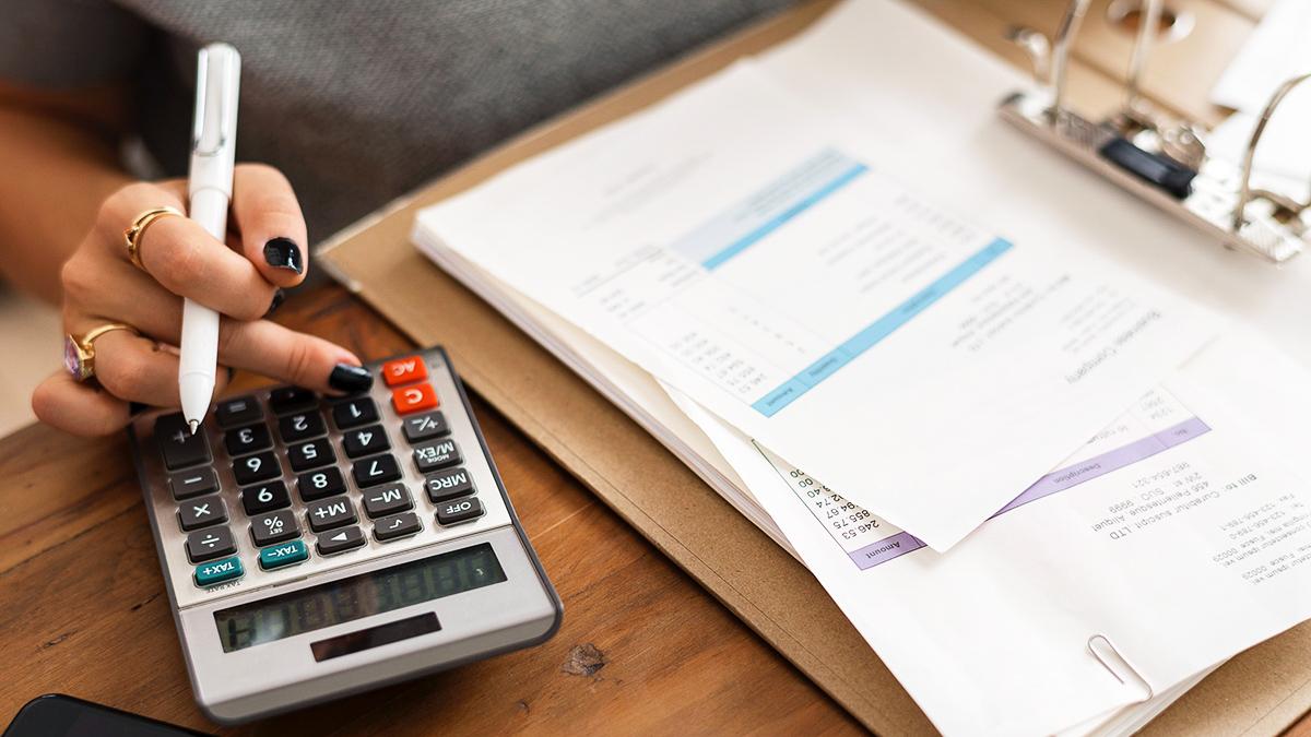 A female is using a calculator at a desk.