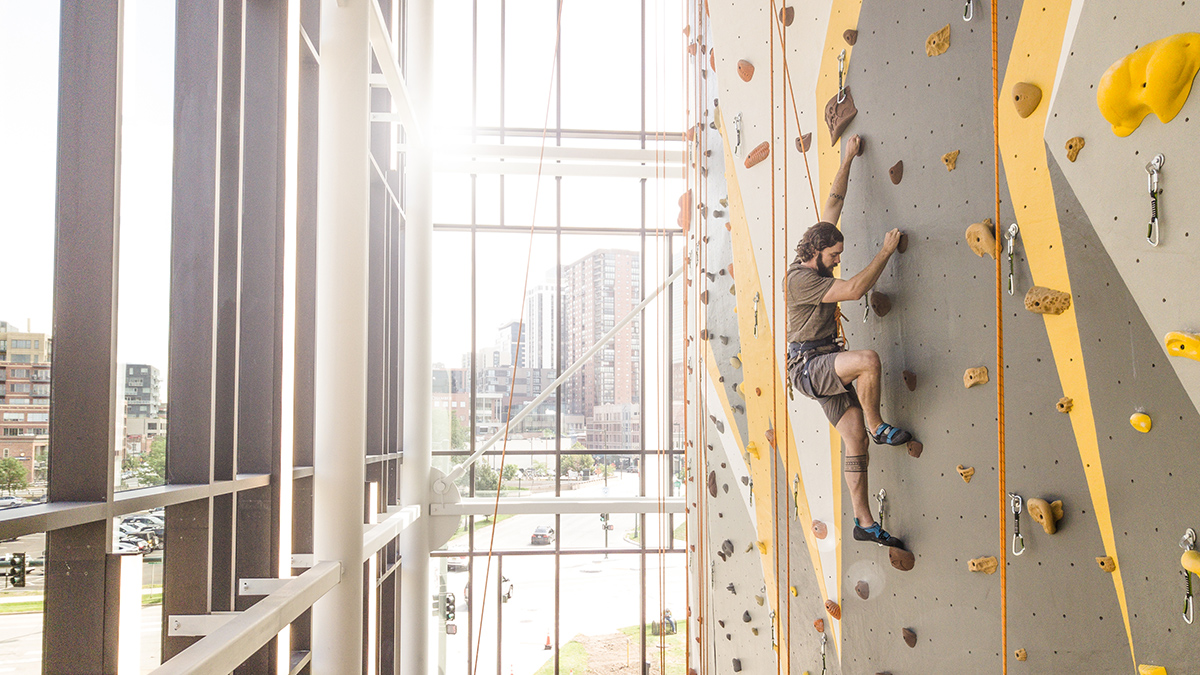 Male on climbing wall in the Student Wellness Center.