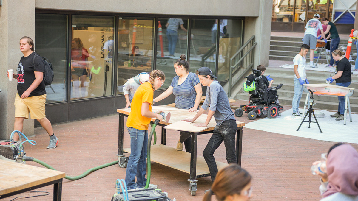 Group of students working outside the CU building to build a bench.