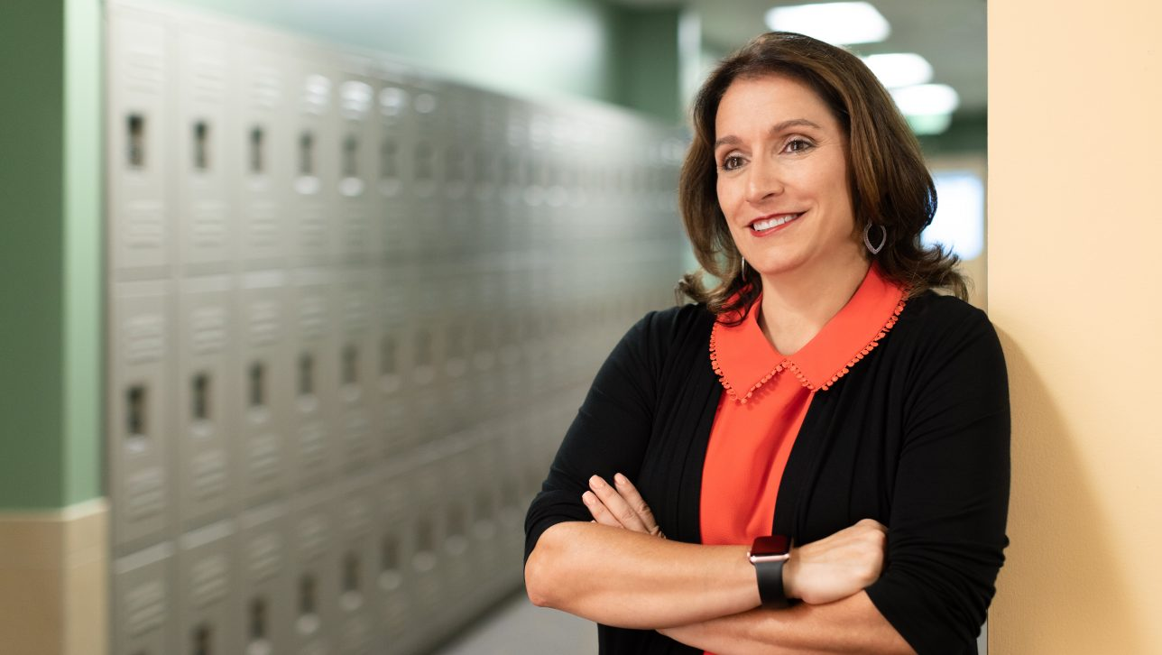 Portrait of Susana Cordova, DPS Superintendent, leaning against row of gray school lockers.