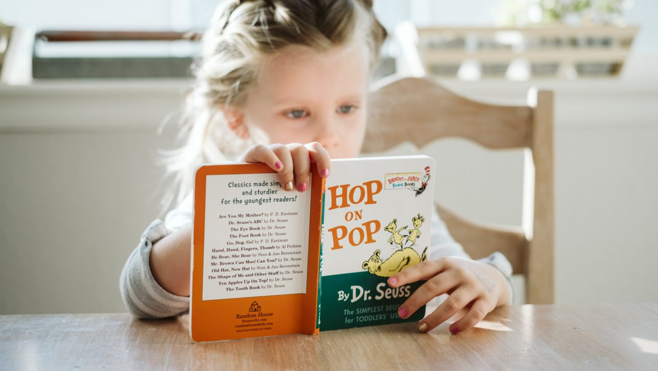 Young girl seated at table reading book by Dr. Seuss titled Hop on Pop. Photo by Josh Applegate on Unsplash.