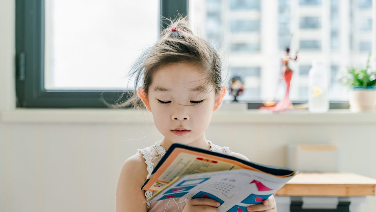 School-aged girl reading a colorful book. Photo by Jerry Wang on Unsplash.